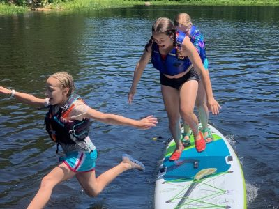 Girl jumping off paddleboard into the river
