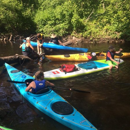 Taking a break at a log jam on the Lamprey River