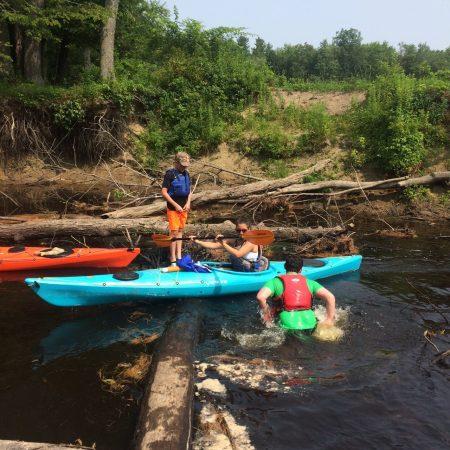 helping kayakers across a log jam