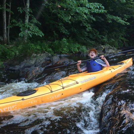 boy sending a kayak over a small waterfall