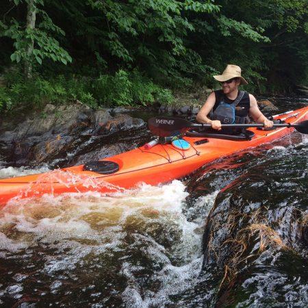 kayaker cruising down a small fall
