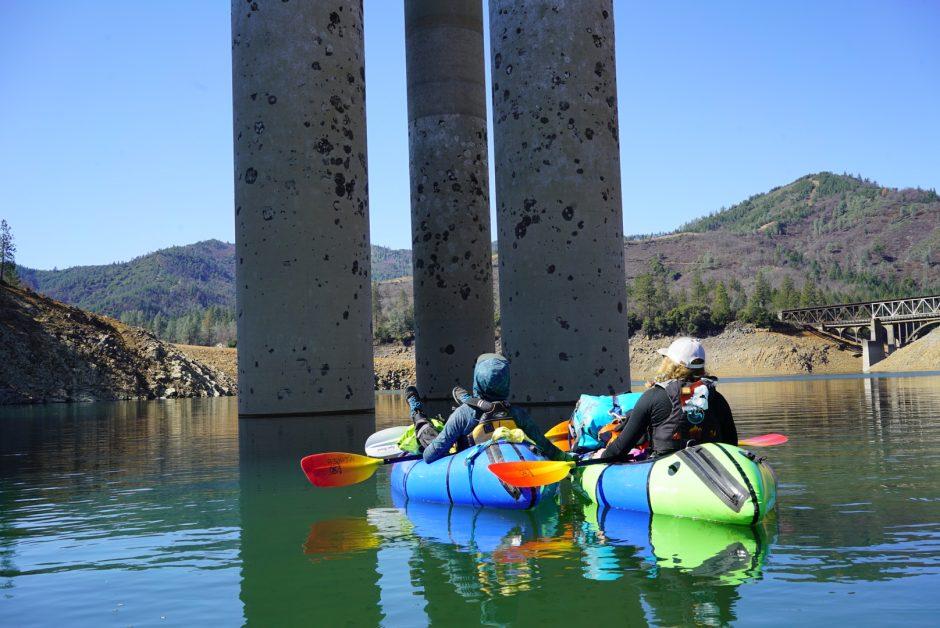 The Team packrafts under a bridge on Shasta Reservoir.